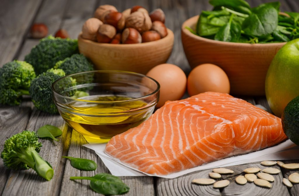 Omega-3 food portrayed through fish, avocado, nuts, and fish oil